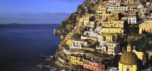View of the city of Positano, with fishing boats on the beach.