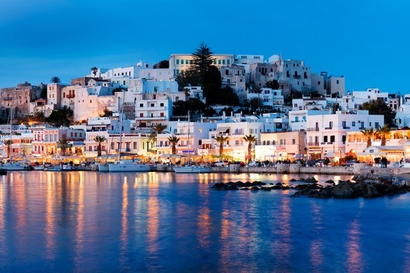 A view of the harbor and boats in Naxos, Greece at sundown.