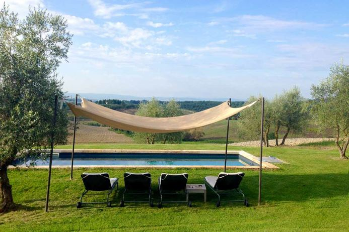 Villa in Tuscany, Italy with pool overlooking hillside vista.
