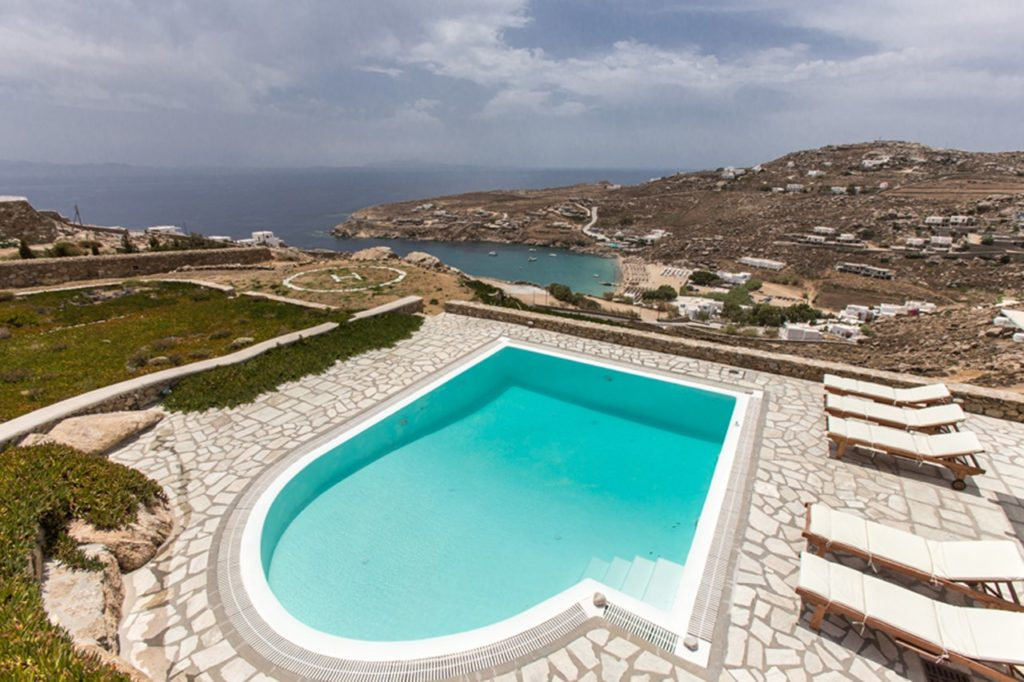 Large water front villa in Mykonos, Greece with a pool and outside sitting area.