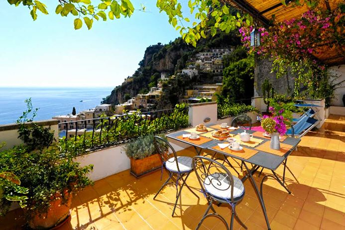Waterfront villa on the Amalfi Coast of Italy with large deck overlooking the sea.